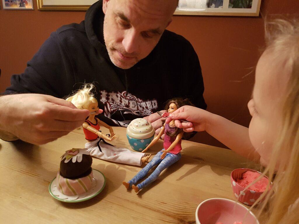 Papa und Tochter spielen mit Barbie