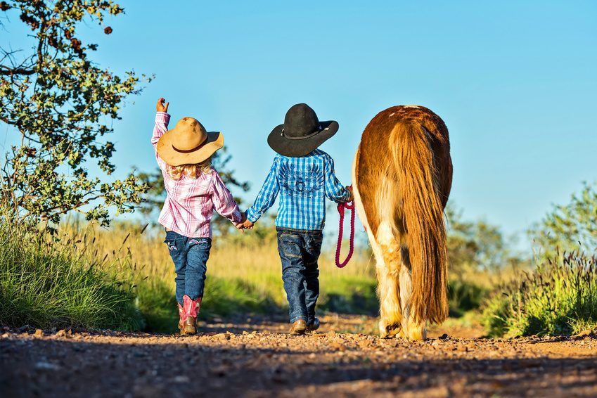 Little cowgirl and cowboy with pony