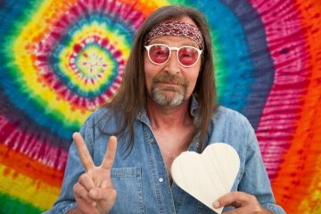 Hippie middle-aged man making the victory sign
